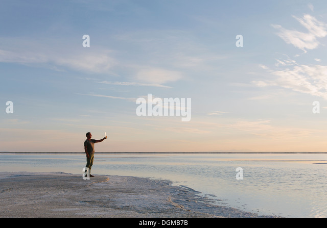 A man standing at edge of the flooded Bonneville Salt Flats at dusk, taking a photograph with a tablet device. - Stock Image