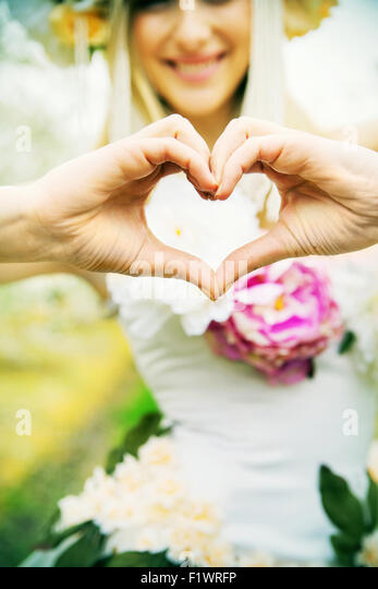 Beautiful joyful woman making the heart sign - Stock Image