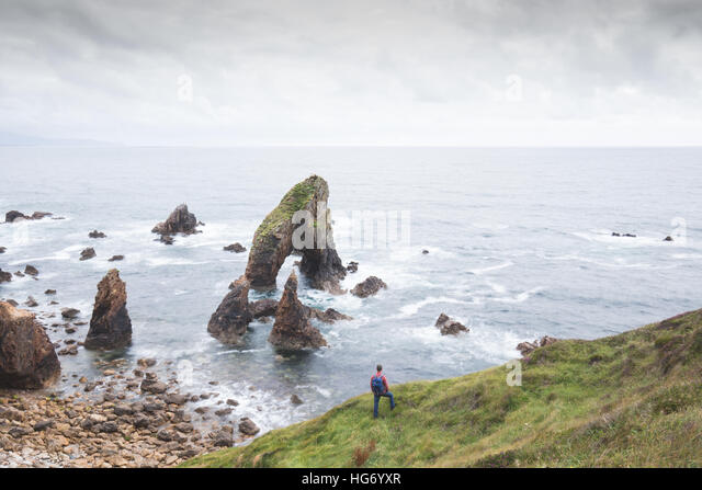 Walker at Crohy Head sea arch, County Donegal, Ireland - Stock-Bilder