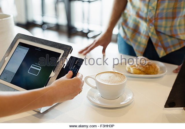 Customer paying for coffee in coffee shop, mid section - Stock Image