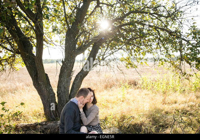 Image of a young couple hugging while sitting under a tree at autumn sunset - Stock-Bilder