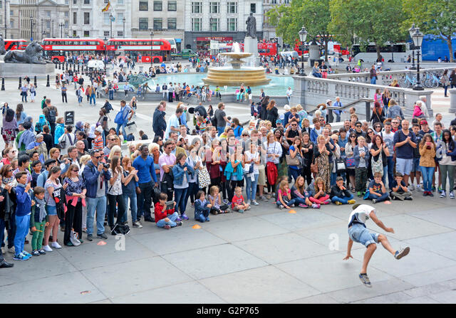 Large crowd of people including tourists gather around street performer gymnastic dancing in front of spectators - Stock Image