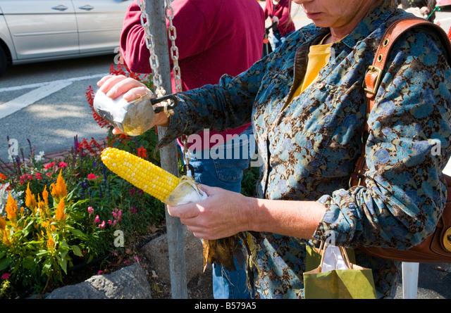 Woman Salting Street Festival Corn - Stock Image