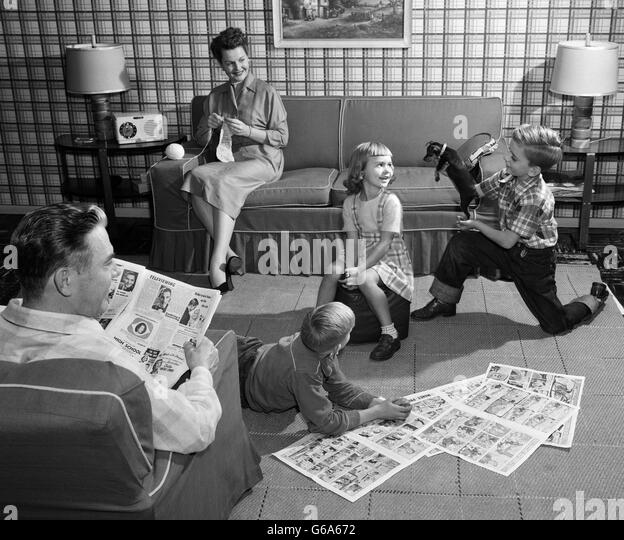 1950s FAMILY 5 LIVING ROOM KIDS ON FLOOR READING COMICS PLAYING WITH DOG MOTHER KNITTING FATHER READING NEWSPAPER - Stock Image