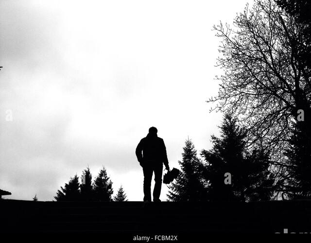 Silhouette Man Standing On Field Against Sky - Stock Image