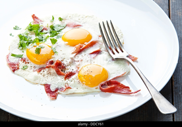 Traditional breakfast with eggs and bacon on white plate - Stock Image