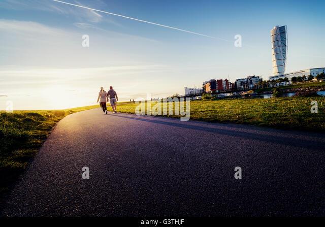 Sweden, Skane, Malmo, Ribersborg, Mid-adult couple holding hands - Stock Image