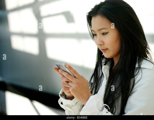 A young Chinese business woman using her mobile phone PDA in the city. - Stock Image