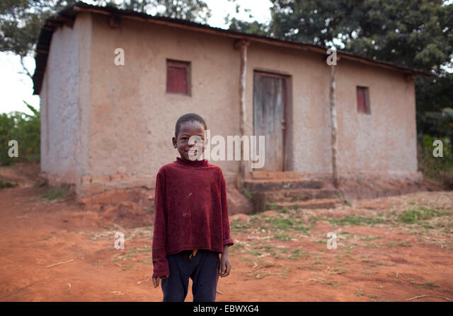 little boy standing in front of a humble house in the country, Burundi, Karuzi, Buhiga - Stock Image