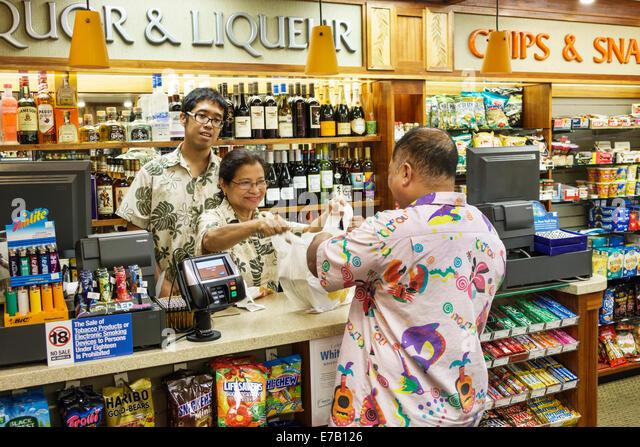 Hawaii Hawaiian Honolulu Waikiki Beach ABC Stores convenience inside Asian man woman customer cashier employee - Stock Image