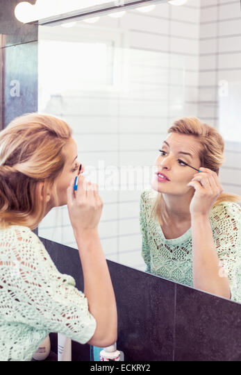 Young woman applying mascara in front of bathroom mirror - Stock Image