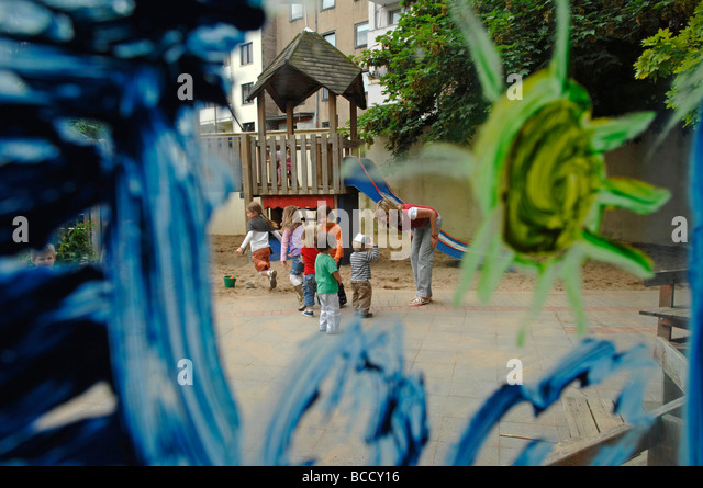 Children and teacher playing on a playground in a kindergarten on a summer day. - Stock Image