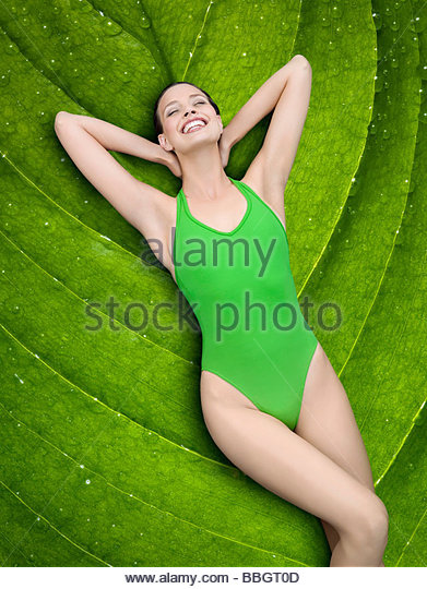 Portrait young woman lying on leaf - Stock Image