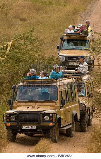 Safari vehicles watching a herd of elephants Serengeti National Park Tanzania - Stock Image