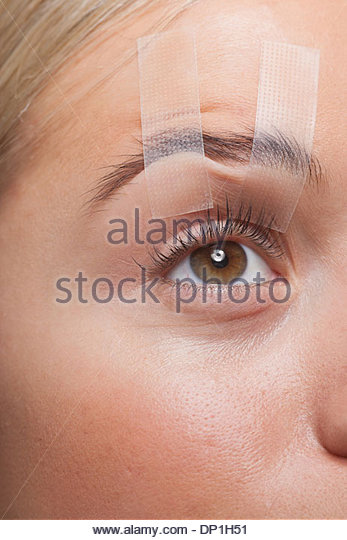 Close up of womanÂ's eye taped open - Stock Image