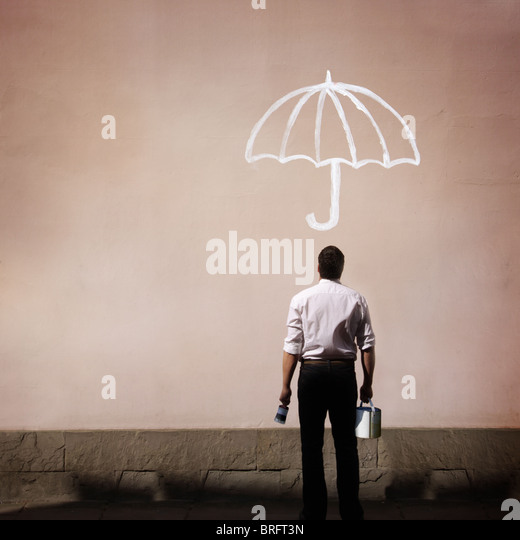 man holding paint pot looking at a wall with umbrella painted on it - Stock-Bilder