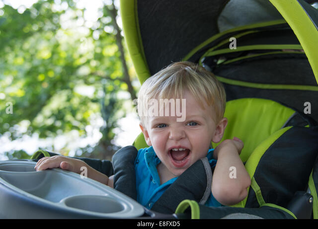 Boy sitting in a stroller laughing - Stock Image