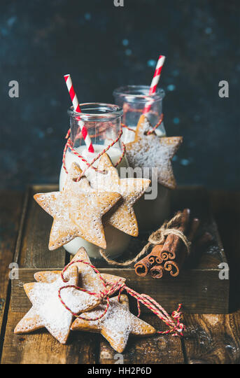 Bottles with milk and Christmas homemade gingerbread star shaped cookies - Stock Image