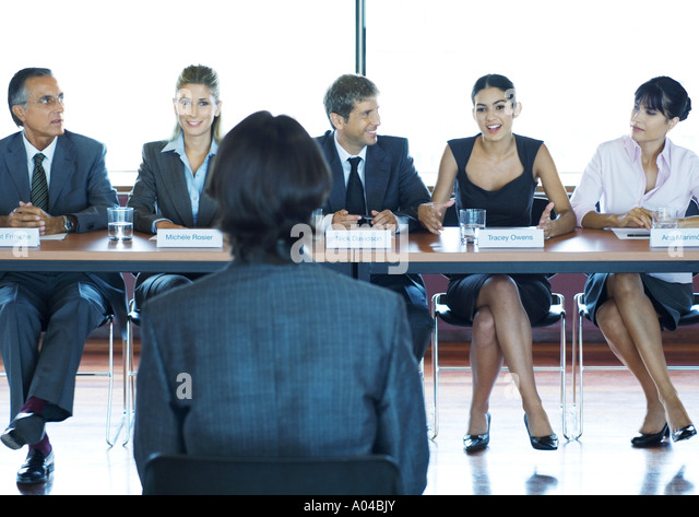 Businesspeople in committee meeting, facing man in foreground - Stock Image