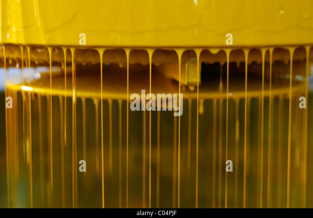 Industrial machinery for paint working with yellow paint - Stock Image