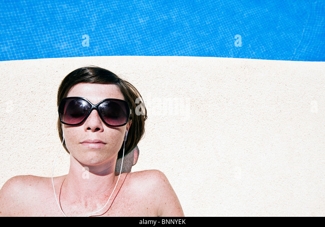 Shot of an Attractive Brown Haired Woman Next to the Pool with her Earphones - Stock Image