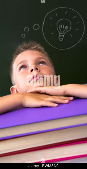Face of diligent schoolboy looking upwards with his head on stack of books over black background - Stock Image