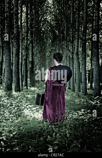a woman is walking through a forest with a hat and a suitcase in a period dress - Stock-Bilder