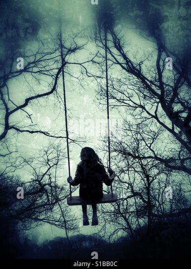 Young girl in swing in the woods - Stock-Bilder