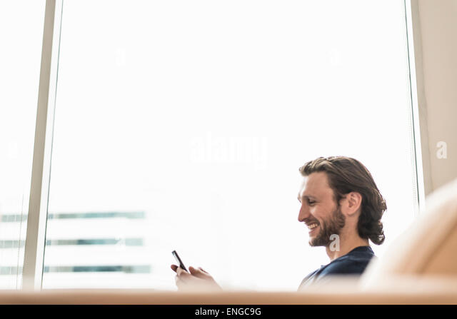 A man seated checking his smart phone and laughing. - Stock Image