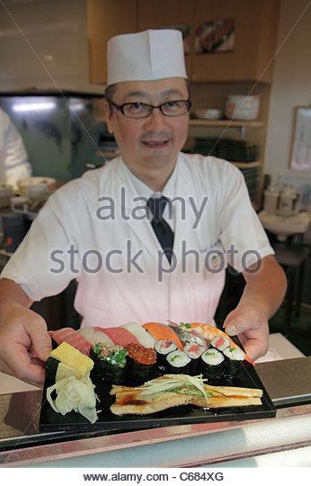 Tokyo Japan Ueno Chuo Dori kanji hiragana katakana Japanese English characters symbols sushi bar restaurant chef - Stock Image