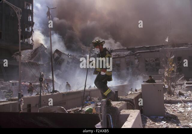 Fire fighters amid smoking rubble following September 11th terrorist attack on World Trade Center. At left is still - Stock-Bilder