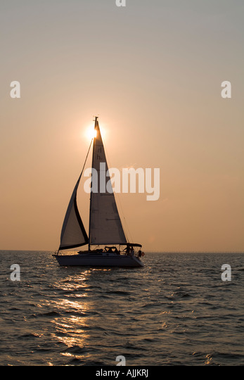 Sailboat on the water at sunrise during Chesapeake Bay Harbor Fest Parade of Sails, Virginia Beach, Virginia - Stock Image