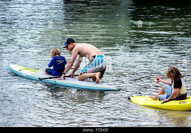 Florida Jupiter Loxihatchee River man father boy children surfboard paddleboard water - Stock Image