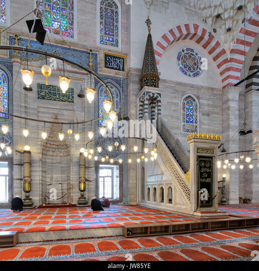 Istanbul, Turkey - April 19, 2017: Marble floral golden ornate minbar (Platform) and niche, with few prayers at - Stock Image