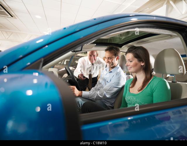 Salesman shows customers a car - Stock Image