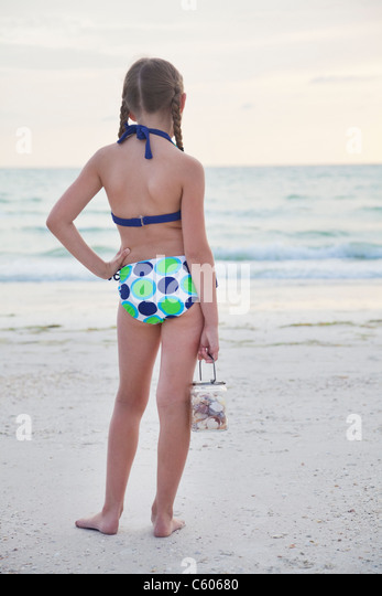 USA, Florida, St. Pete Beach, Rear view of girl (8-9) holding jar of seashells on beach - Stock Image