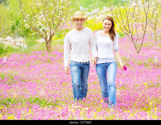 Two cheerful lovers walking in spring garden, having fun outdoors, relaxation on backyard, romance and love concept - Stock-Bilder