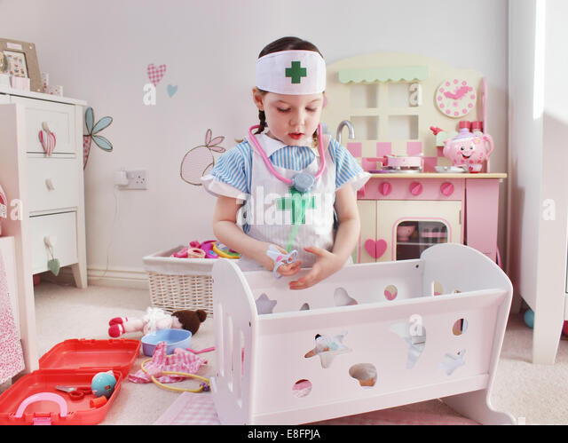 Girl dressed as a nurse playing - Stock Image