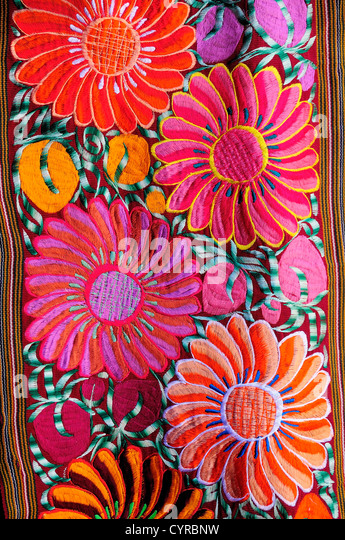 Mexico, Bajio, San Miguel de Allende, Brightly coloured embroidered floral textile hanging outside arts shop with - Stock Image