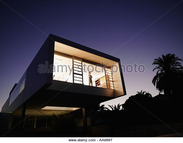 Exterior of a modern office building with man looking out window - Stock-Bilder