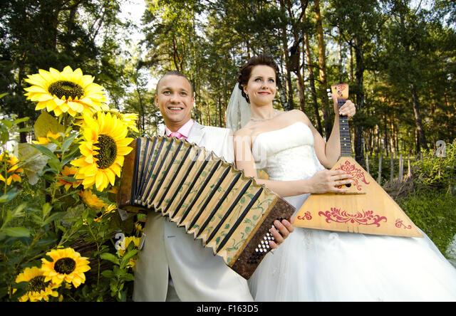 fiancee blow the balalaika,  bridegroom play on accordion, wedding  humour photo - Stock Image
