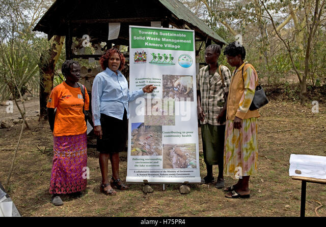 Four women with waste management poster Kamere Kenya - Stock Image