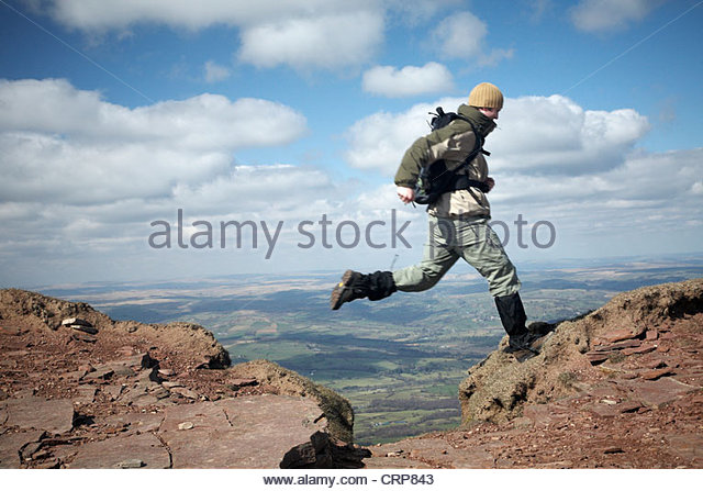 A walker leaping over a gap in a path on Pen Y Fan, the highest peak in South Wales. - Stock Image