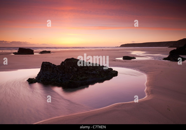 Rockpools on the sandy shores of Bedruthan Steps at sunset Cornwall, England. Spring (May) 2011. - Stock Image
