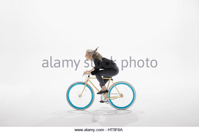 Woman riding bicycle against white background - Stock-Bilder