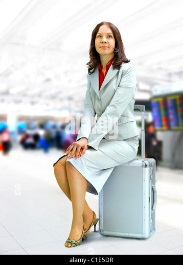young businesswoman sits on silver suitcase in airport - Stock Image