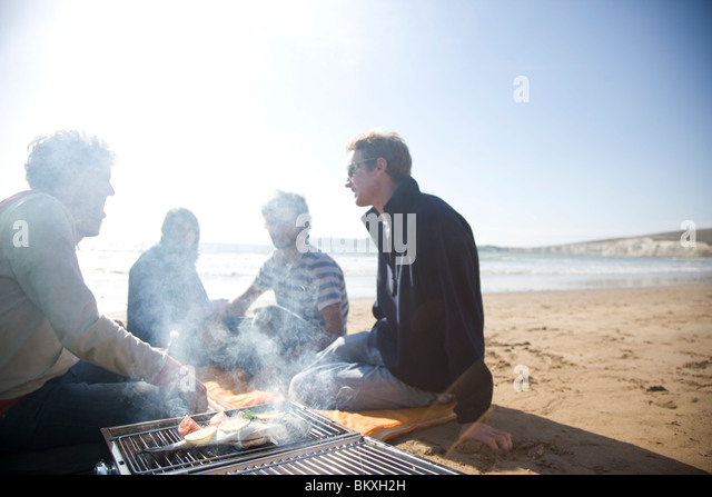 Group of friends sitting around a barbeque on the beach - Stock Image