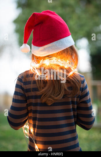 A little girl dressed in a santa hat and fairy Christmas lights - Stock Image