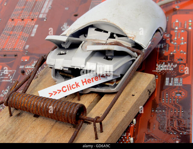 Computer mouse caught in a trap, with the bait Click here in its mouth. - Stock Image