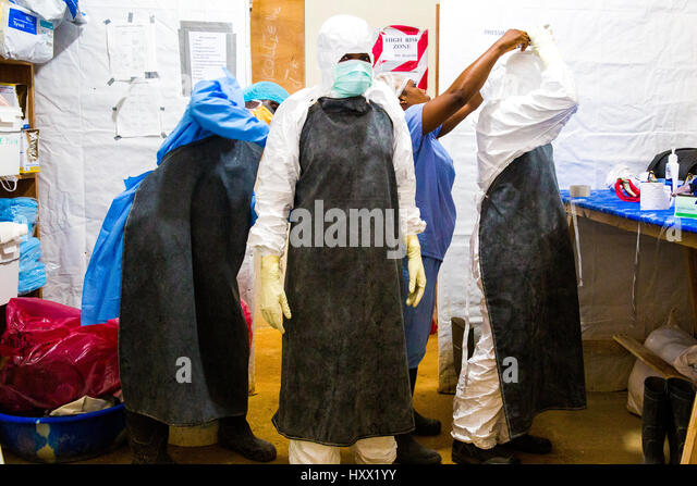 Health care workers get dresses in protective clothing (PPE) in preparation for their shift with their patients - Stock Image
